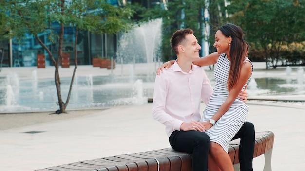 Romantisches gemischtrassiges paar mit einer date-frau, die ihrem freund etwas ins ohr flüstert