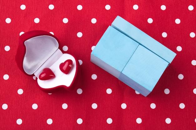 Romantisches geschenkkonzept rote schmuckschatulle mit herzen und blauer schachtel auf rot gepunktetem hintergrund
