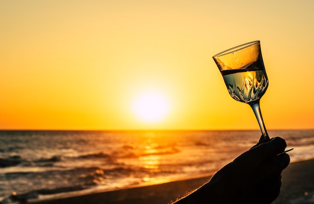 Romantisches glas wein am strand in orange himmel und sonne