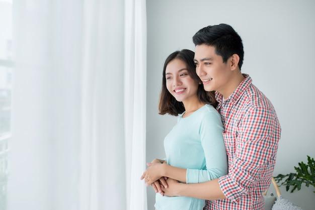 Romantisches glückliches junges asiatisches paar entspannen sich im modernen zuhause drinnen