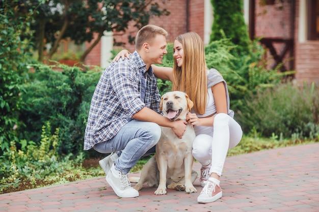 Romantisches glückliches paar in der liebe, die ihre zeit mit labrador in der natur genießt.