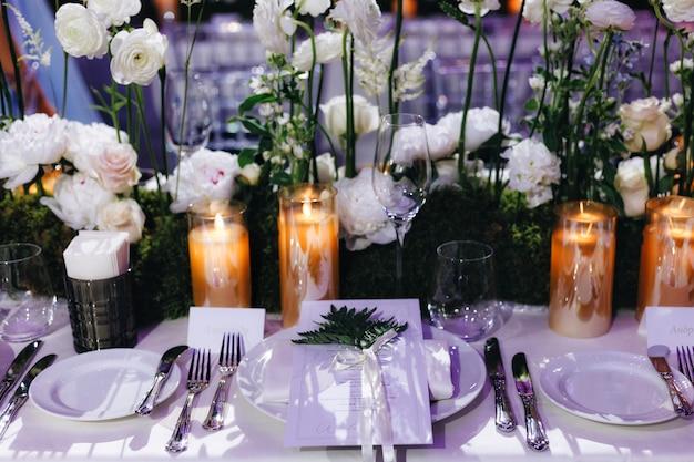 Romantisches hochzeits-tischplatten-layout-dekor mit großen üppigen blumensträußen, darunter weiße rosen, ranunkeln, persische butterblumen, weiße orchideen und kerzen. foto in hoher qualität