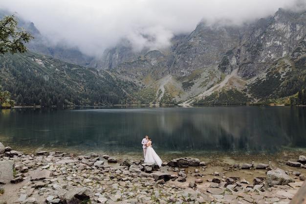 Romantisches hochzeitspaar im liebesstand des seeaugensees in polen. tatra berge.