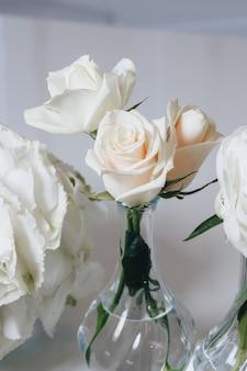 Romantisches hochzeitstischdekorationsdekor mit großen üppigen blumensträußen einschließlich weißer rosen ranunc ...