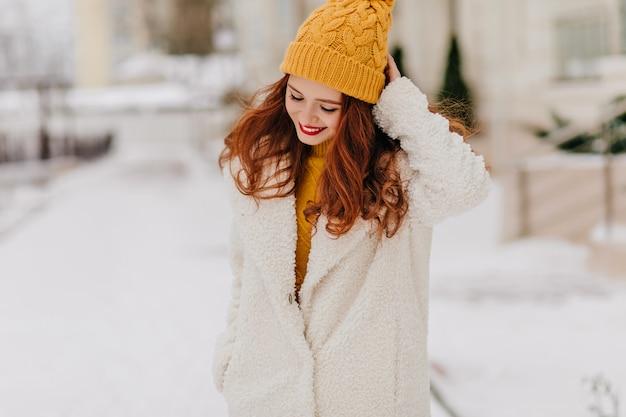 Romantisches ingwermädchen, das während des fotoshootings im freien nach unten schaut. anmutige kaukasische dame, die im winter durch stadt geht.