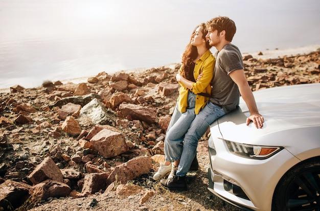 Romantisches junges attraktives paar, das den sonnenuntergang beobachtet und mit sportwagen küsst.