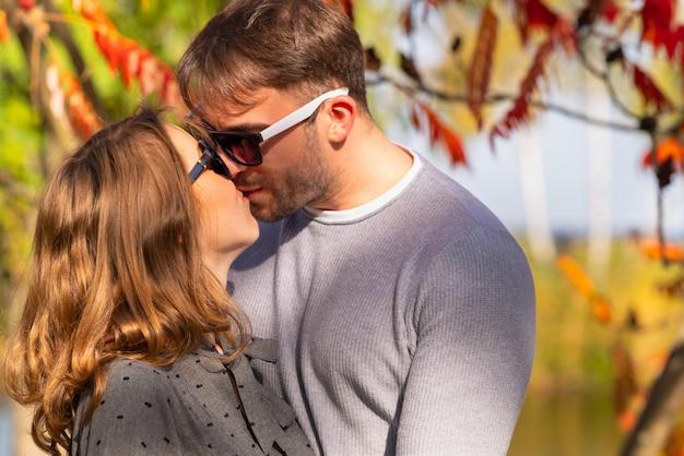 Romantisches junges coupé, das im herbst im garten vor einem bunten hintergrund der herbstblätter küsst