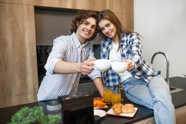 Romantisches junges ehepaar, das kaffee in der modernen wohnküche mit zwei tassen trinkt.