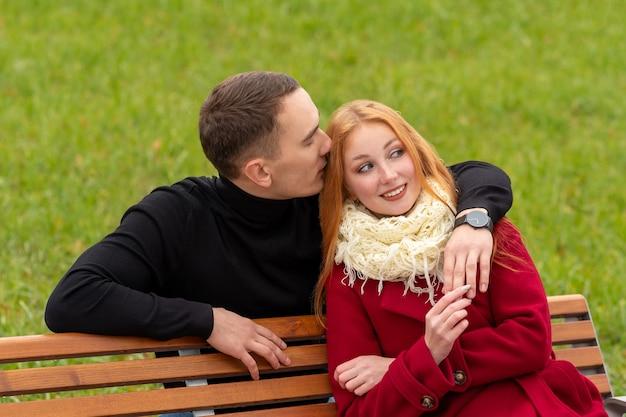Romantisches junges paar auf einer parkbank, der typ flüstert dem mädchen ins ohr