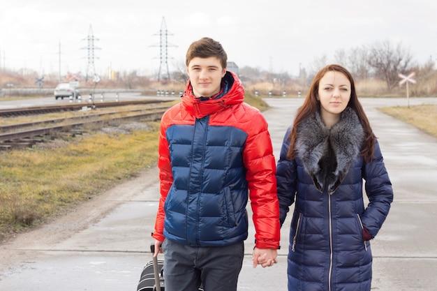 Romantisches junges paar, das einen koffer trägt, während sie hand in hand eine landstraße entlang gehen, während sie gemeinsam in den urlaub oder in die flitterwochen aufbrechen