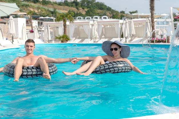 Romantisches junges paar, das händchen in einem schwimmbad hält, während sie nebeneinander auf gummischläuchen schweben und die sonne im sommerurlaub genießen