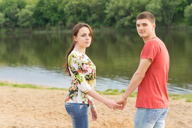Romantisches junges paar, das hand in hand steht