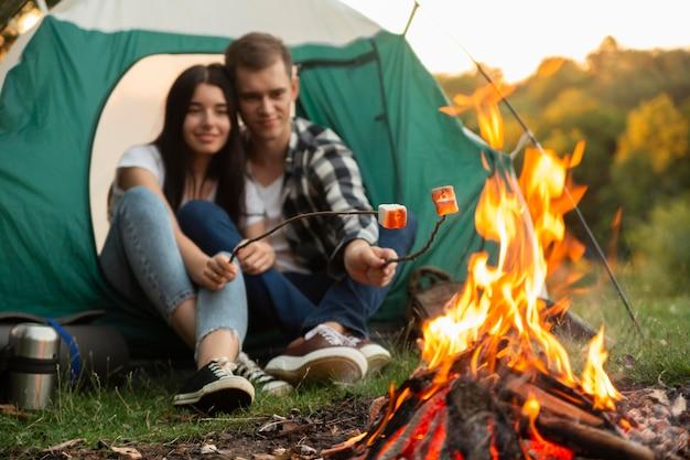 Romantisches junges paar, das lagerfeuer genießt