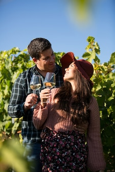 Romantisches junges paar, das sich ansieht und gläser weißwein in einem weinberg hält. verliebtes paar in der reihe eines weinbergs.