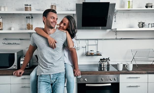 Romantisches junges paar in der küche. attraktive junge frau und hübscher mann genießen, zeit zusammen zu verbringen, während sie auf heller moderner küche stehen.