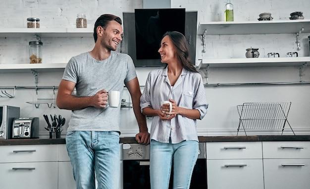 Romantisches junges paar in der küche trinken kaffee. attraktive junge frau und hübscher mann genießen, zeit zusammen zu verbringen, während sie auf heller moderner küche stehen.