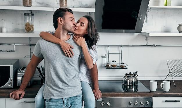 Romantisches junges paar küsst in der küche. attraktive junge frau und hübscher mann genießen, zeit zusammen zu verbringen, während sie auf heller moderner küche stehen.