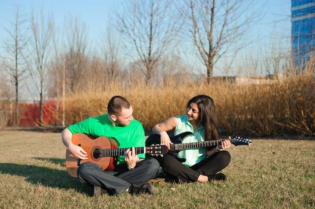 Romantisches junges paarporträt, das gitarre unter blauem himmel spielt,