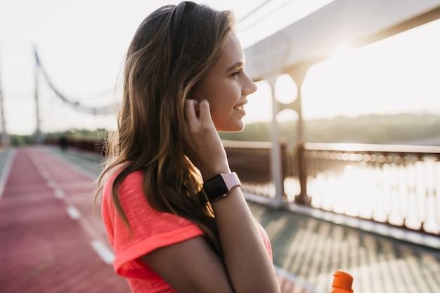 Romantisches kaukasisches mädchen trägt smartwatch, die am stadion aufwirft. außenaufnahme der freudigen jungen frau, die morgen nahe fluss verbringt.