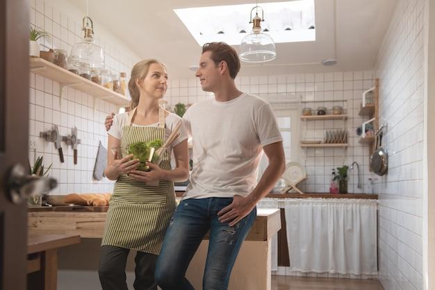 Romantisches kaukasisches paar in der liebe, die große zeit zusammen in der küche hat. glücklicher junger mann und frau in der küchenhand halten schlag des salats und schauen einander mit lächelndem gesicht an.