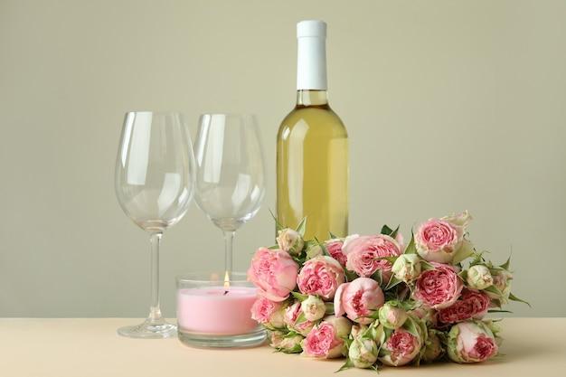 Romantisches konzept mit rosen, wein und kerze auf beigem tisch