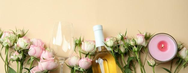 Romantisches konzept mit rosen, wein und kerzen auf beige