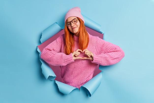Romantisches konzept. zufriedene liebevolle rothaarige frau tut herz symbol oder liebeszeichen formen herz mit fingern schließt augen mit vergnügen trägt rosa hut und pullover bricht durch papierwand
