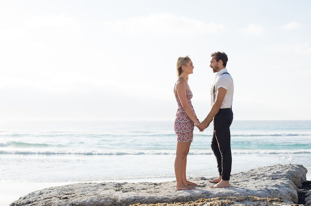 Romantisches lässiges junges paar, das hände hält und am strand steht