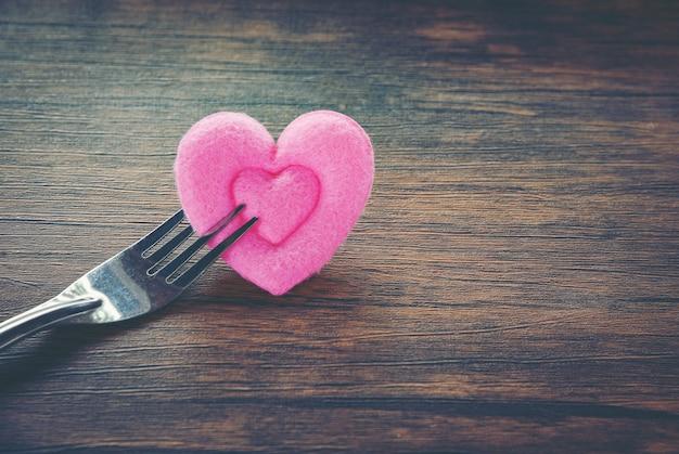Romantisches liebesessen des valentinsgrußessens und liebe, die konzept kochen romantische tabelleneinstellung verziert mit gabel und rosa herzen auf hölzernem