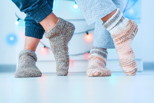 Romantisches liebesfamilienpaar in warm gestrickten weichen kuscheligen socken im winter zu hause