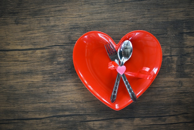 Romantisches liebeskonzept der valentinsgrußabendessen romantische tabelleneinstellung verziert mit gabellöffel in der roten herzplatte auf hölzernem