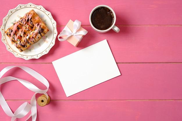 Romantisches liebeskonzept. leere papierkarte, rolle mit band, geschenkbox, tasse kaffee, leckerer kuchen auf rosa holzhintergrund. draufsicht, flache komposition, oben