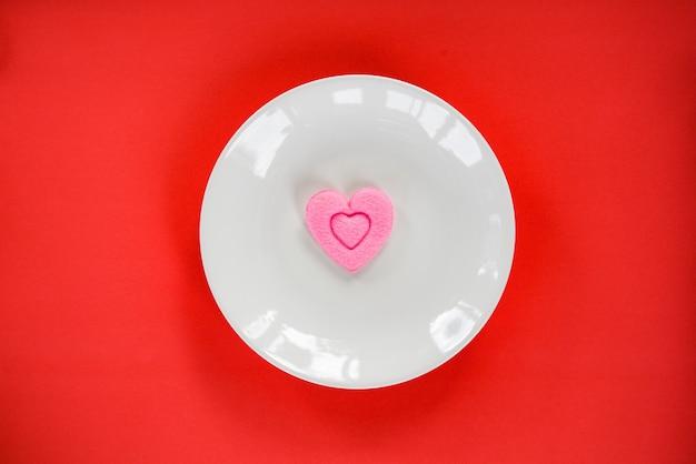 Romantisches liebeslebensmittel des valentinsgrußessens, das rosa herz auf platte kocht