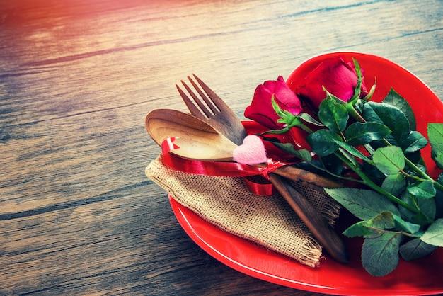Romantisches liebeslebensmittel des valentinsgrußessens und liebe, die kochen romantische tabelleneinstellung verziert mit hölzernen gabellöffelrosen in der roten herzplatte
