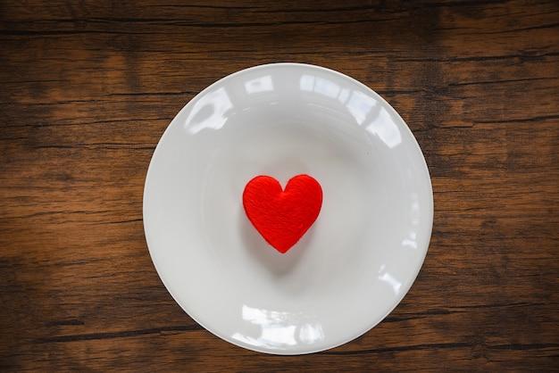Romantisches liebeslebensmittel des valentinsgrußessens und liebe, die kochen rotes herz auf der romantischen tabelleneinstellung der weißen platte verziert mit dem roten herzen hölzern