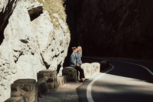 Romantisches liebespaar, das auf der straße mit felsen und steinen geht.