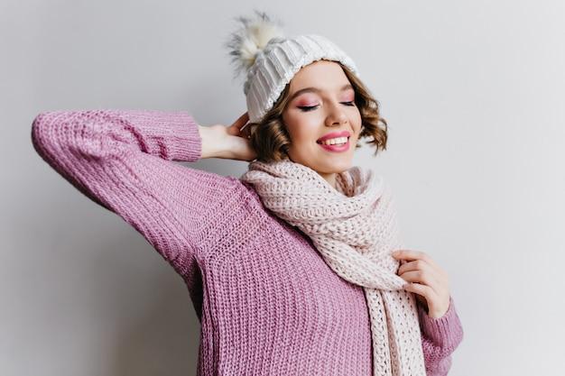 Romantisches lockiges mädchen im weißen hut, der rosa geschenkbox hält und lächelt. frohe dame mit kurzem haarschnitt, der weihnachtsgeschenk mit glücklichem gesichtsausdruck betrachtet.