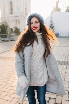 Romantisches mädchen im langen strickpullover, der mit lächeln während des morgenspaziergangs im dezember aufwirft. gut aussehende brünette frau im grauen mantel und in den blauen jeans, die im winter in der stadt chillen.