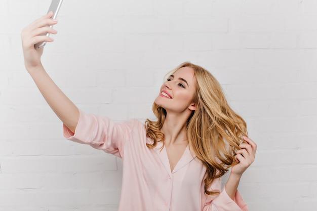 Romantisches mädchen mit schüchternem lächeln, das selfie beim spielen mit blonden haaren macht. innenporträt der reizenden jungen frau im rosa pyjama, das bild von sich auf weißer wand macht.
