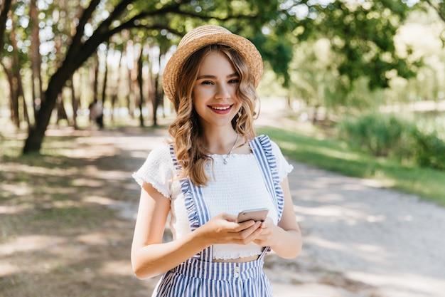 Romantisches mädchen trägt hut und weißes t-shirt, das auf natur lächelt. entzückende blondhaarige frau, die spaziergang im park genießt.