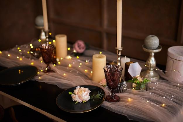 Romantisches oder hochzeitsessen oder feiertagstisch, braune, rosa und goldene dekoration mit kerzen und girlandenlicht. nahaufnahme details, selektiver fokus