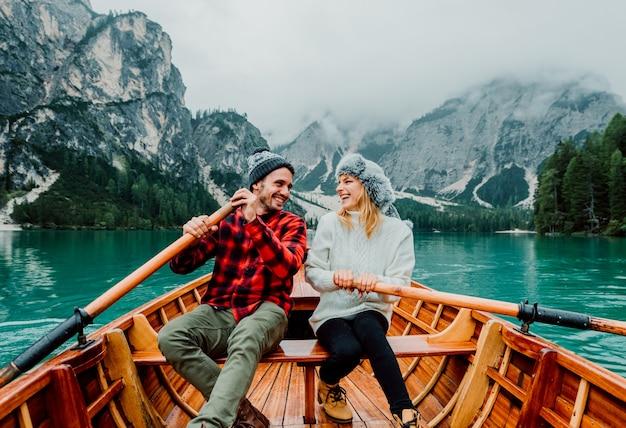 Romantisches paar auf einem boot, das einen alpensee bei braies italien besucht.