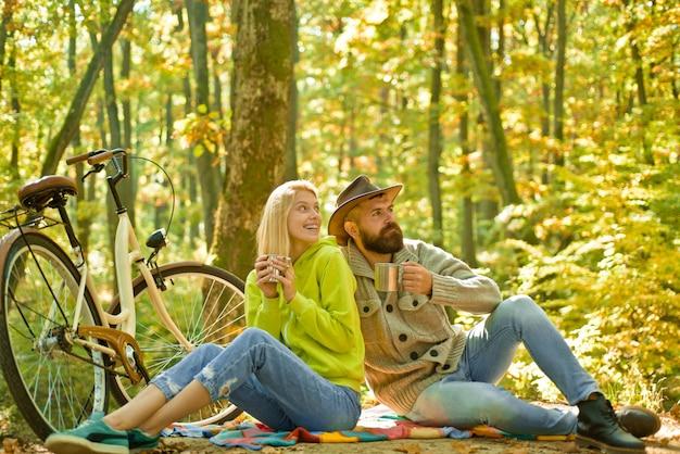 Romantisches paar beim date. datum und liebe. herbst-dattelwanderung im wald. romantisches date mit fahrrad. verliebte paare fahren zusammen fahrrad im waldpark. bärtiger mann und frau, die sich im herbstwald entspannen.