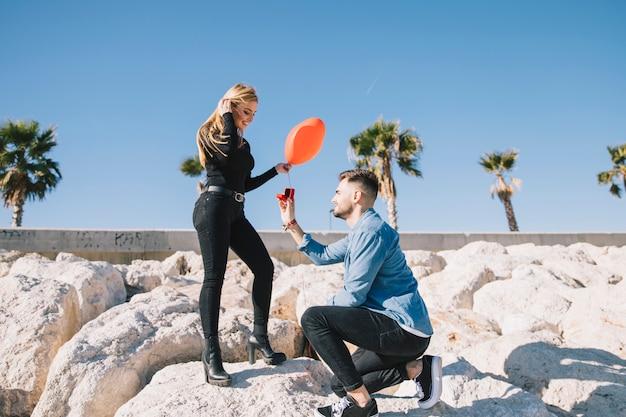 Romantisches paar, das an schöner küstenlinie teilnimmt