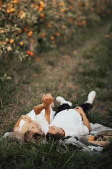 Romantisches paar, das auf einer picknickdecke neben einem korb mit trauben und weißwein liegt, einander ansieht und hände hält.