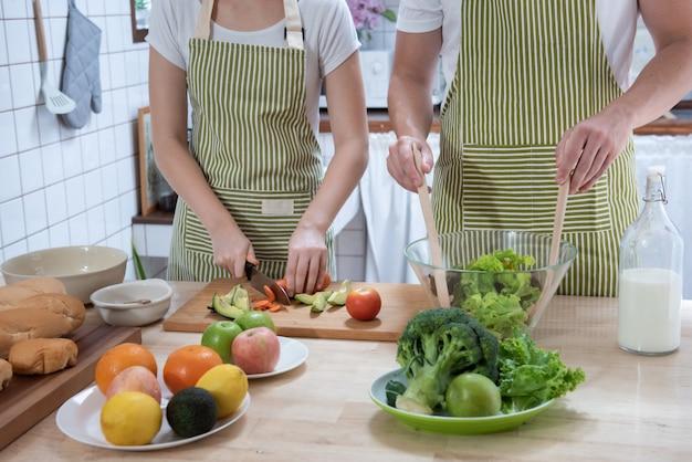 Romantisches paar, das auf küche zu hause kocht. hübscher junger kaukasischer mann und attraktive junge frau, die spaß zusammen beim bilden des salats haben. gesundes lebensstilkonzept.