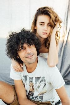 Romantisches paar, das bei sonnenuntergang umarmt. im hintergrund ist ein graues tuch