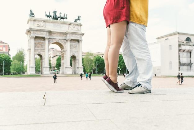 Romantisches paar, das den sonnenuntergang genießt, die denkmäler im stadtzentrum beobachtet und küsst