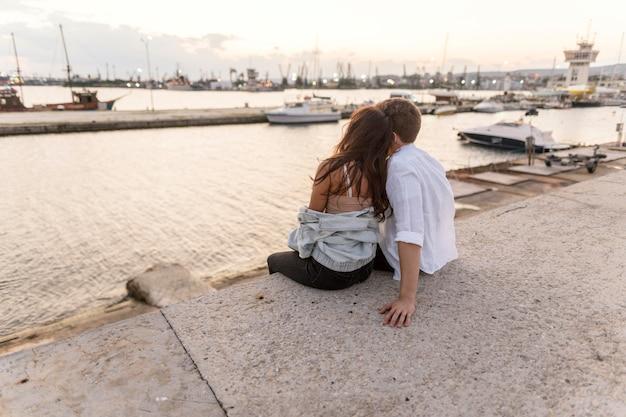 Romantisches paar, das die ansicht zusammen bei sonnenuntergang genießt