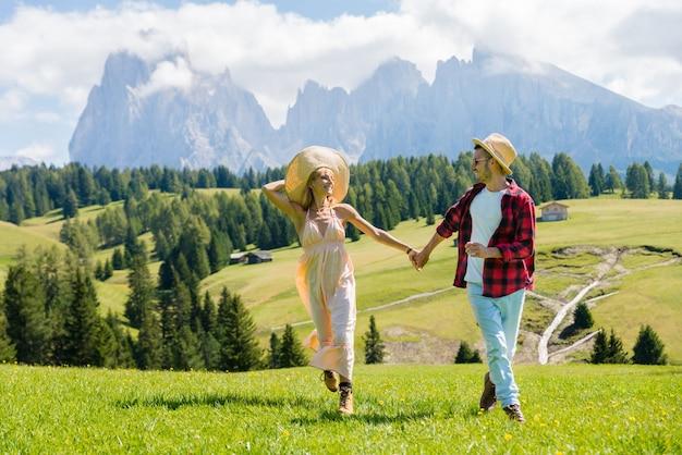 Romantisches paar, das die freiheit genießt, die auf dem hügel läuft